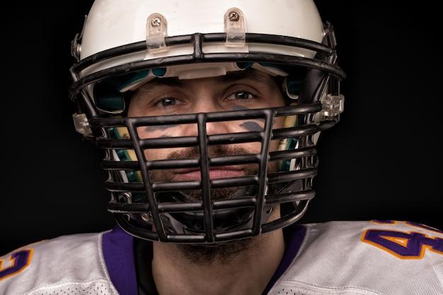 Portrait gros plan, joueur de football américain, barbu en casque.