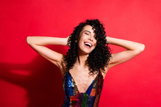 Portrait en gros plan d'une magnifique fille aux cheveux ondulés gaie s'amusant isolée sur fond de couleur rouge vif brillant éclatant
