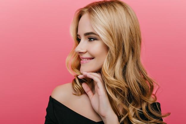 Portrait de gros plan de la magnifique jeune femme aux cheveux brillants isolé sur un mur rose. photo intérieure d'une fille extatique aux cheveux blonds regardant ailleurs avec un sourire doux.