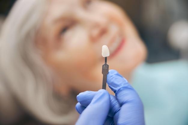 Portrait en gros plan d'une main portant un gant bleu tenant une dent en porcelaine au cabinet dentaire professionnel