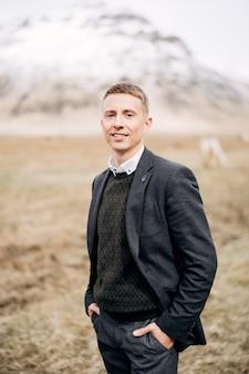 Portrait en gros plan d'un marié sur fond de montagne enneigée en islande