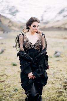 Portrait en gros plan d'une mariée vêtue d'une robe noire avec un manteau noir et un maquillage grossier se dresse dans un champ