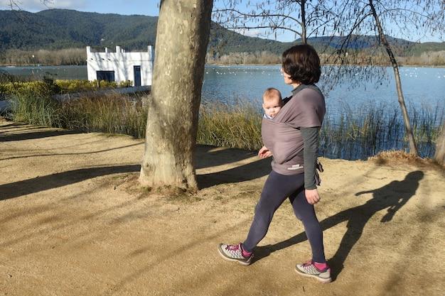 Portrait en gros plan d'une mère qui exerce en portant son fils à l'extérieur