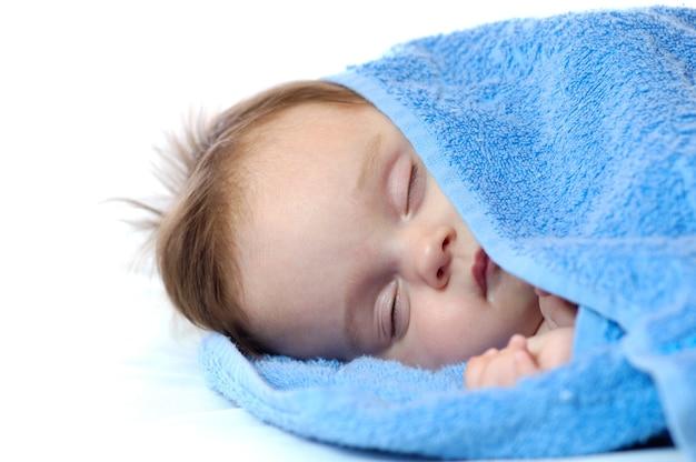 Portrait en gros plan d'une mignonne petite fille dormir dans la serviette bleue sur fond blanc. concept de sommeil sain pour bébé.