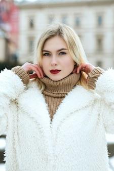 Le portrait en gros plan d'un modèle attrayant porte un manteau posant à la ville