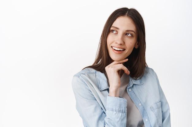 Portrait en gros plan d'un modèle féminin élégant et réfléchi, toucher le menton et regarder le coin supérieur gauche pensif, voir l'offre promotionnelle intéressante, lire la bannière du logo, debout sur un mur blanc