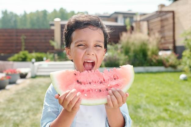 Portrait en gros plan moyen d'un petit garçon joyeux debout dans l'arrière-cour en train de manger un morceau de pastèque