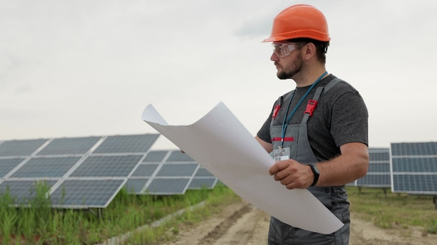 Portrait en gros plan d'un ouvrier électrique masculin dans un casque de protection apprenant la conception du plan papier de l'usine solaire. énergie propre. industrie. concept d'énergie verte.