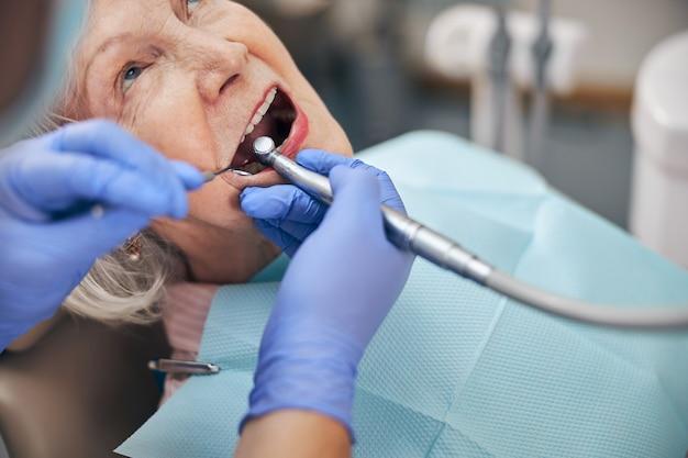Portrait en gros plan d'un patient assis sur le fauteuil dentaire pendant que le dentiste à la procédure tenant une fraise dentaire dans une clinique dentaire moderne