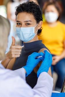 Portrait en gros plan d'une patiente heureuse portant un masque facial assis regarder la caméra montrer le pouce vers le haut pendant que dans la file d'attente de vaccination reçoit une injection de vaccin à partir d'une aiguille de seringue par le médecin.