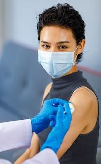 Portrait en gros plan d'une patiente portant un masque facial assis en regardant la caméra tandis que le médecin porte une blouse de laboratoire blanche et des gants en caoutchouc à l'aide d'une aiguille de seringue et de coton injectant le vaccin contre le coronavirus.