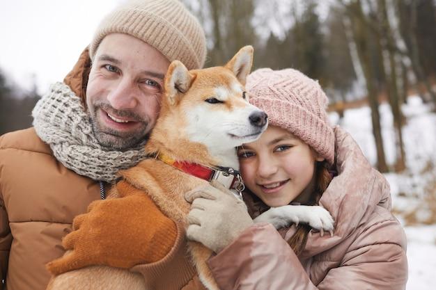 Portrait en gros plan d'un père et d'une fille heureux câlins avec un chien tout en profitant d'une promenade en plein air ensemble dans la forêt d'hiver