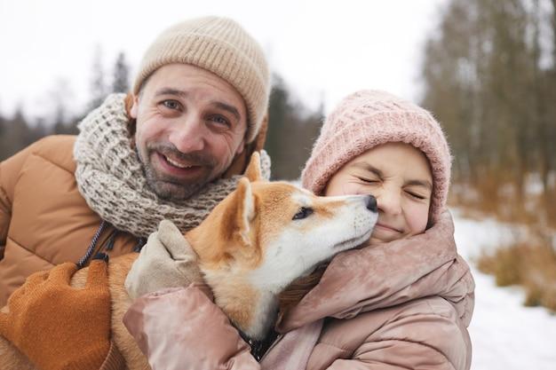 Portrait en gros plan d'un père et d'une fille heureux jouant avec un chien tout en profitant d'une promenade en plein air ensemble dans la forêt d'hiver