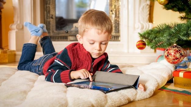 Portrait en gros plan d'un petit garçon allongé sur le sol dans le salon décoré pour noël et jouant sur une tablette numérique