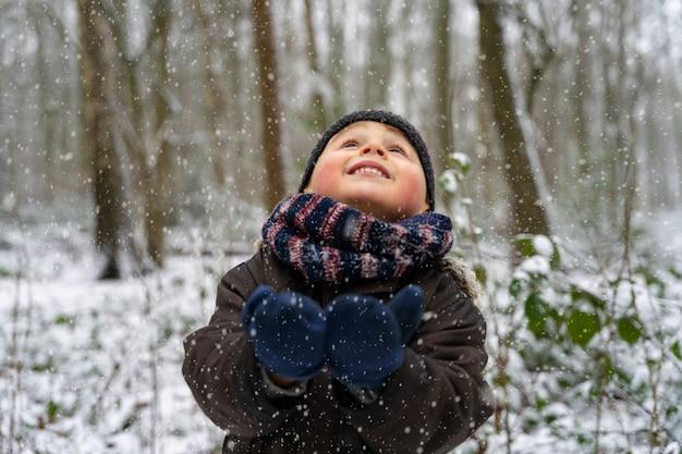 Portrait en gros plan d'un petit garçon jouant avec des flocons de neige dans un parc en hiver. un enfant heureux profite de la première neige dans une forêt.