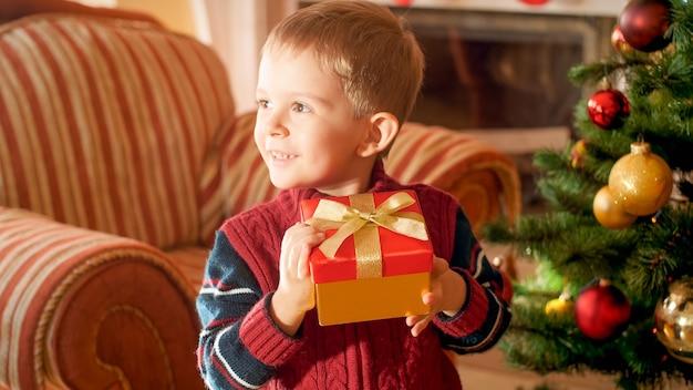 Portrait en gros plan d'un petit garçon souriant joyeux et joyeux avec un cadeau de noël rouge attaché par un arc de ruban doré