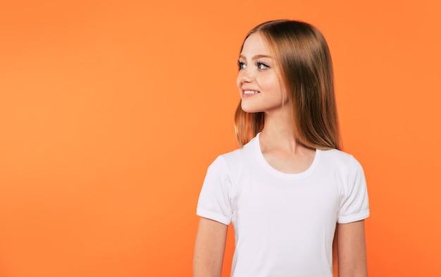 Portrait en gros plan d'une petite fille blonde attirante et mignonne aux cheveux longs pendant qu'elle pose isolée en studio et souriante