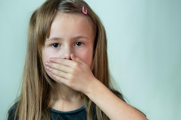 Portrait de gros plan de petite fille enfant aux cheveux longs couvrant sa bouche avec les mains.