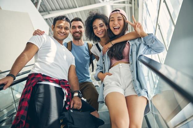 Portrait en gros plan de quatre personnes sympathiques souriantes en se tenant debout sur l'escalier mobile