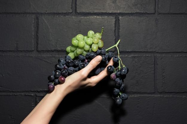Portrait en gros plan de raisins dans une main féminine, sur le mur de briques sombres.