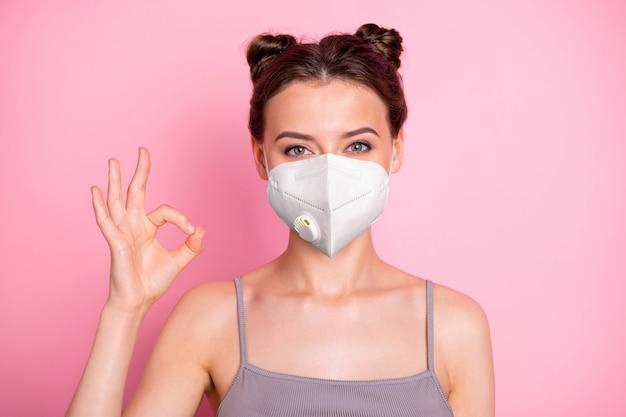 Portrait en gros plan de sa jolie fille portant un masque respiratoire réutilisable n95 arrêter la décontamination maladie cov mers prévention grippe montrant ok-signe isolé sur fond de couleur pastel rose