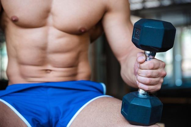 Portrait en gros plan d'une séance d'entraînement d'homme tenant l'haltère dans la salle de fitness