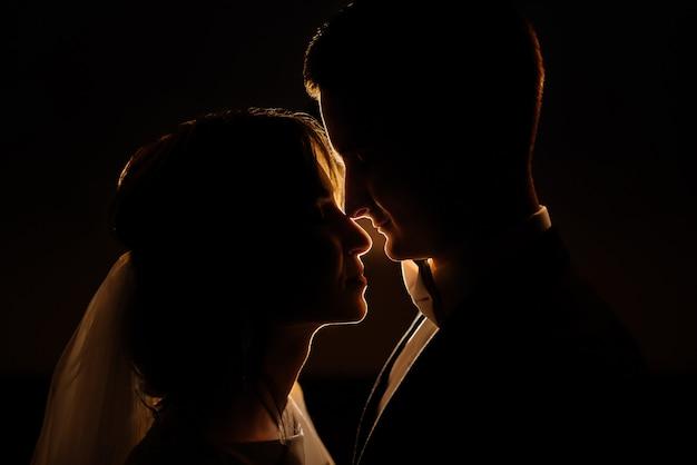 Portrait de gros plan d'une silhouette de couple romantique avec un rétro-éclairage la nuit. idée photo créative de la photographie de mariage la nuit. silhouette d'une mariée et d'un marié éclairée par des lumières.