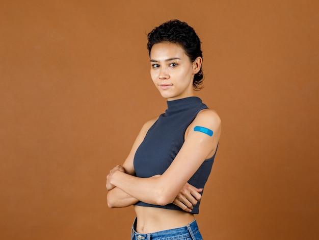 Portrait gros plan en studio photo d'une jolie belle patiente sexy souriante montrant un bandage en plâtre bleu sur son épaule après avoir reçu la vaccination contre le coronavirus covid-19 devant le mur marron.