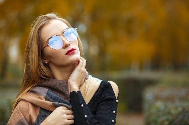 Portrait en gros plan d'une superbe femme blonde aux cheveux longs portant des lunettes. espace pour le texte