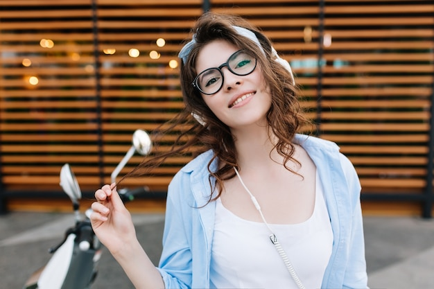 Portrait en gros plan d'une superbe fille joyeuse aux cheveux brun foncé jouant avec ses boucles et souriant timide