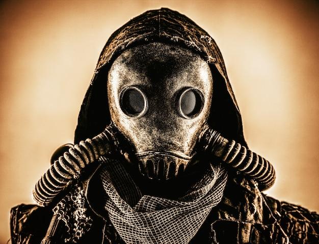 Portrait en gros plan d'un survivant nucléaire post-apocalypse, d'un mutant ou d'une créature souterraine vivant, d'un harceleur qualifié portant des chiffons et d'un masque à gaz intégral blindé ou d'un appareil respiratoire à air, tournage tonique