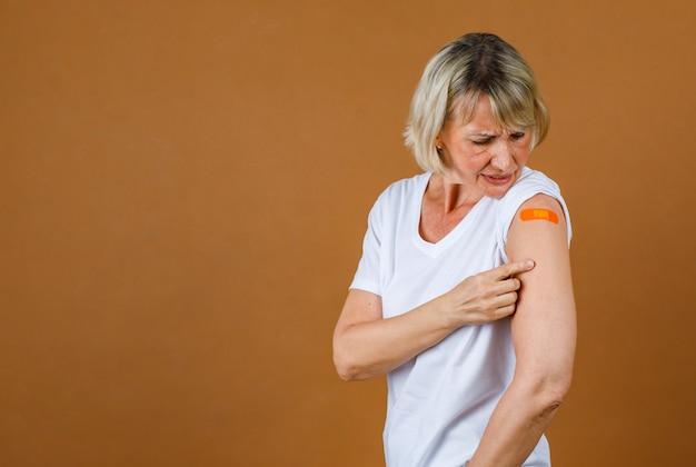 Portrait gros plan tourné en studio d'une patiente blonde âgée de race blanche, soulignant qu'elle souffre d'une blessure par injection au pansement de plâtre orange sur son épaule après avoir reçu la vaccination covid-19.