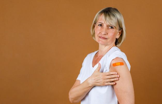 Portrait gros plan tourné en studio d'une patiente blonde senior du caucase soulignant qu'elle souffre d'une blessure par injection au pansement de plâtre orange sur son épaule après avoir reçu la vaccination covid-19.