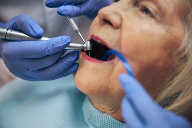 Portrait en gros plan de l'utilisation d'une fraise dentaire pour les dents du patient en cabinet dentaire dans une procédure de traitement dentaire