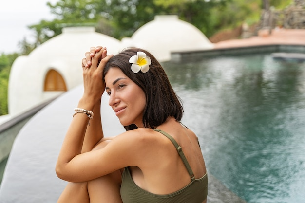 Portrait en gros plan d'un vacancier avec une fleur de plumeria dans les cheveux regardant au loin