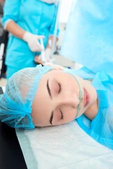 Portrait en gros plan vertical d'une jeune femme subissant une intervention chirurgicale à l'infirmière médicale de l'hôpital faisant une injection