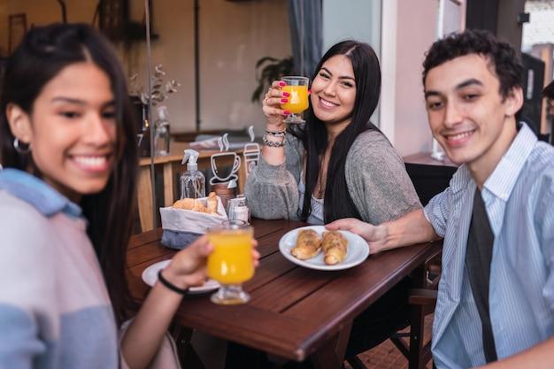 Portrait d'un groupe d'amis buvant des jus dans un bar.