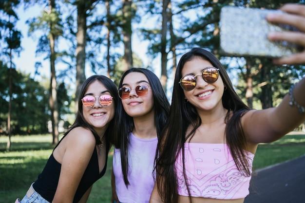 Portrait d'un groupe de beaux amis adolescents avec des lunettes de soleil prenant un selfie