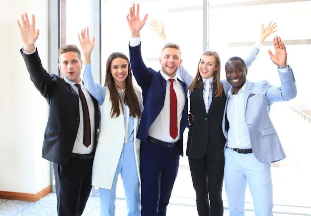Portrait d'un groupe d'entreprises prospère, agitant les mains au bureau