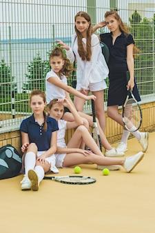 Portrait de groupe de filles en tant que joueurs de tennis tenant une raquette de tennis contre l'herbe verte de la cour extérieure