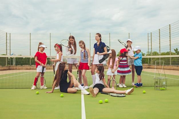 Portrait de groupe de filles en tant que joueurs de tennis tenant une raquette de tennis