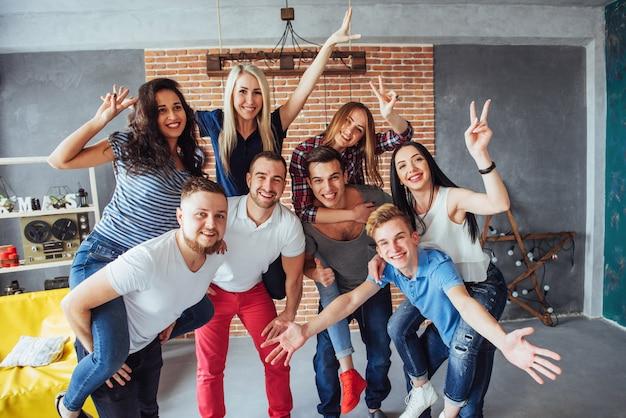 Portrait de groupe de garçons et filles multiethniques avec des vêtements à la mode colorés, tenant un ami posant sur un mur de briques, gens de style urbain s'amusant, s à propos du style de vie de la jeunesse