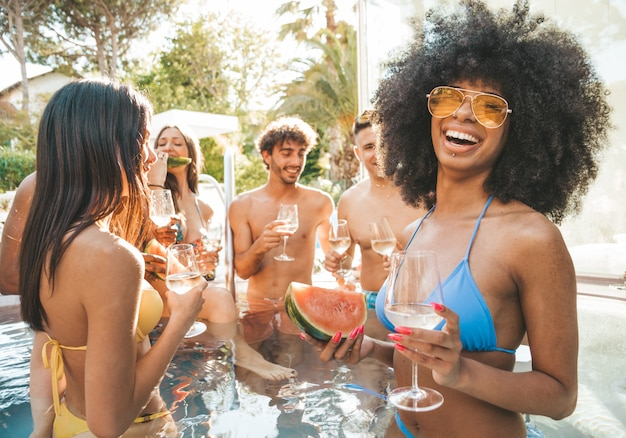 Portrait de groupe de jeunes s'amusant à la piscine, boire du vin de champagne.