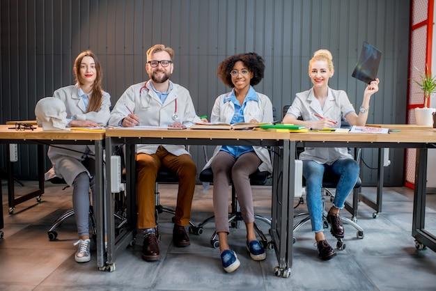 Portrait d'un groupe multiethnique d'étudiants en médecine en uniforme assis ensemble au bureau dans la salle de classe moderne