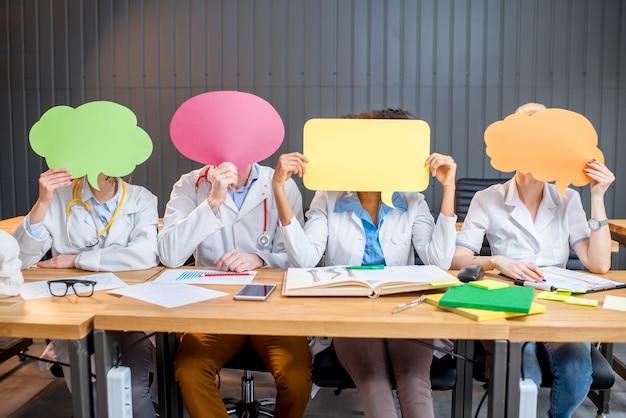 Portrait d'un groupe multiethnique d'étudiants en médecine en uniforme tenant des nuages colorés assis dans une rangée au bureau dans la salle de classe moderne