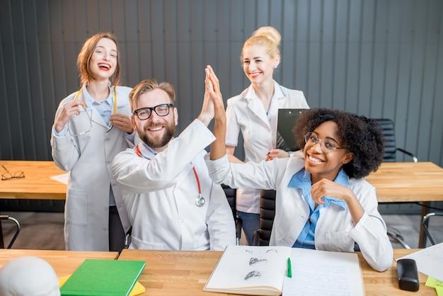 Portrait d'un groupe multiethnique heureux de scientifiques médicaux ou d'étudiants assis ensemble au bureau ou en classe