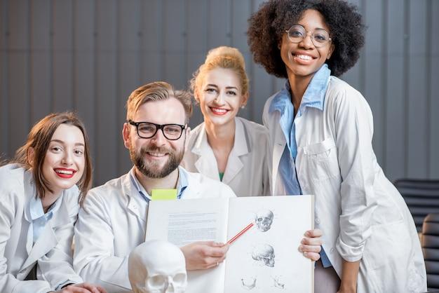 Portrait d'un groupe multiethnique heureux de scientifiques médicaux ou d'étudiants assis avec un livre au bureau ou en classe
