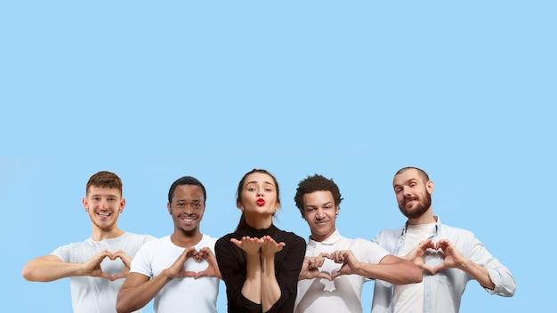 Portrait d'un groupe multiethnique de jeunes isolés sur fond bleu studio flyer