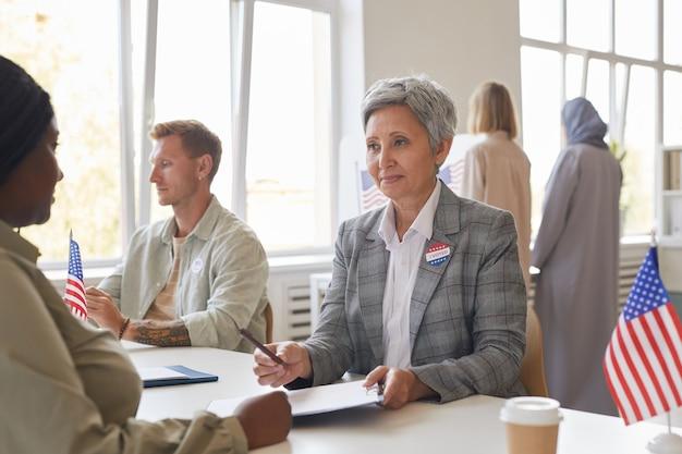 Portrait de groupe multiethnique de personnes votant au bureau de vote décoré de drapeaux américains, copy space