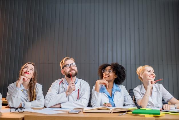 Portrait d'un groupe multiethnique réfléchi d'étudiants en médecine en uniforme assis ensemble au bureau dans la salle de classe moderne